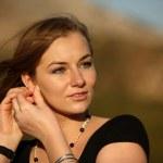 velmi hezká mladá žena, stanovení její náušnice — Stock fotografie