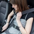 Road safety concept - Pretty young woman fastening her seat belt — Stock Photo