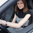 Pretty young woman driving her new car (shallow DOF; color toned — Stock Photo #7420800