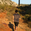 Stock Photo: Runner moving through sunlit landscape.