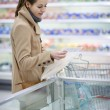 Pretty young woman buying groceries in a supermarket — Stock Photo #7421931