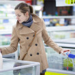 Pretty young woman buying groceries in a supermarket — Stock Photo