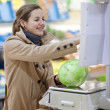 Beautiful young woman shopping for fruits and vegetables — Stock Photo