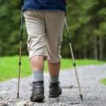 Active handsome senior man nordic walking outdoors — Stock Photo