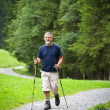 Active handsome senior man nordic walking outdoors — Stock Photo #7422030