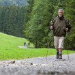 Active handsome senior man nordic walking outdoors — Stock Photo #7422058