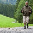 Active handsome senior man nordic walking outdoors — Stock Photo #7422060