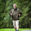 Active handsome senior man nordic walking outdoors — Stock Photo #7422062