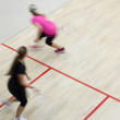 Two female squash players in fast action on a squash court — Stock Photo #7422381