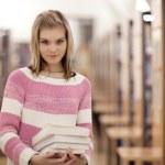 Pretty female college student in a llibrary — Stock Photo