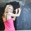 Pretty young college student erasing the chalkboard/blackboard — Zdjęcie stockowe