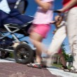 Stock Photo: Mother with small children and a pram crossing a street