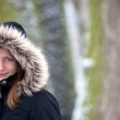 Pretty young woman outdoors in a prk on a snowy winter day — Stock Photo