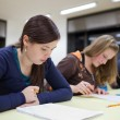 Pretty female college student sitting an exam in a classroom — Stock Photo #7423270