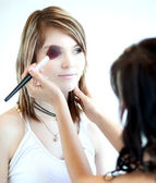 Pretty young woman having powder applied by a make-up artist/bea — Stock Photo