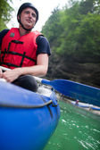 White water rafting - handsome young man in a boat during a halt — Stock Photo
