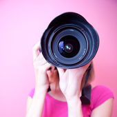 Female photographer pointing her super wide lens at you (color t — Stock Photo