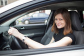 Pretty young woman driving her new car (shallow DOF; color toned — Stock Photo