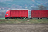 Red camion/truck goes fast on a road — Stock Photo