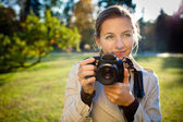 Pretty female photographer outdoors on a lovely day — Stock Photo