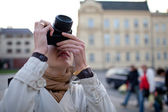 Prety female tourist taking pictues in a city (shallow DOF; sele — Stock Photo