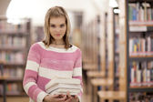 Pretty female college student in a llibrary — Stock Photo