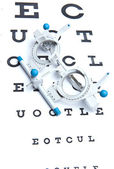 Optometry concept - sight measuring spectacles & eye chart — Stockfoto