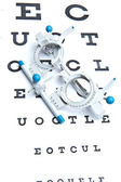 Optometry concept - sight measuring spectacles & eye chart — Stock Photo
