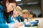 Estudante muito feminino, sentado em uma sala de aula — Foto Stock