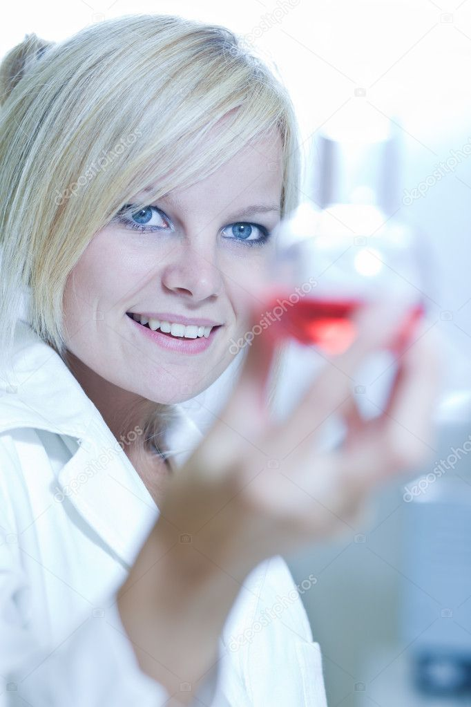 Closeup of a female researcher holding a beaker, carrying out experiments in a chemistry lab  Stock Photo #7420159