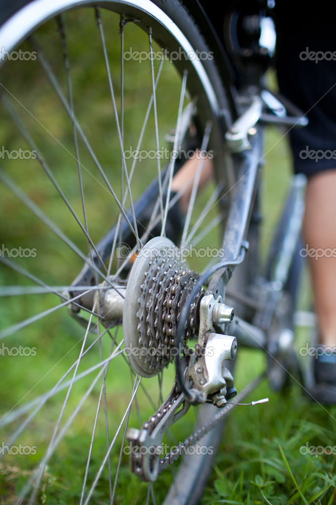 Biking - rear wheel of a young woman's mountain bike on a green mountain path (shallow DOF - selective focus)  Stock Photo #7420214