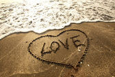 Love concept handwritten on sand — Stockfoto