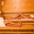 Sauna two women relaxing lying wrapped towel — Stock Photo