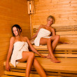 Sauna two women relaxing sitting wrapped towel - Stock Photo