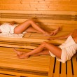 Sauna two women relaxing lying wrapped towel — Stock Photo #6812672
