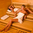 Sauna two women relaxing lying wrapped towel — Stock Photo #6812675