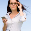 Businesswoman blue sky attractive look with phone — Stock Photo