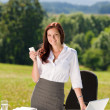 Businesswoman in sunny nature office calling — Stock Photo