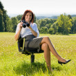Businesswoman sit in sunny meadow seek binocular — Stock Photo