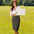 Businesswoman sunny meadow hold empty banner — Stock Photo #6813314