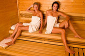 Sauna two women relaxing sitting wrapped towel — Stock Photo