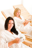 Beauty spa relax two women on sun-beds — Stock Photo