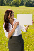 Businesswoman sunny meadow look at empty banner — Stock Photo