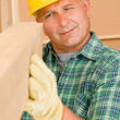 Handyman mature carpenter measure wooden beam - Stock Photo