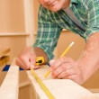 Handyman home improvement close-up of measure wood - Stock Photo