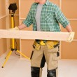 Handyman carpenter mature carry wooden beam — Stock Photo #6879430