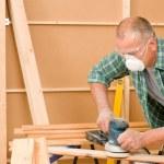 Handyman sanding wooden board diy home renovation — Stock Photo
