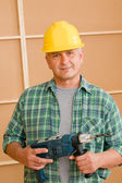 Handyman home improvement with hand drill — Stock Photo