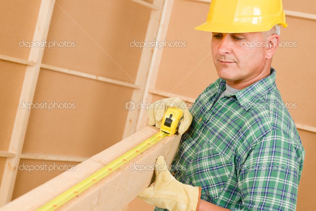 Handyman mature carpenter measures wooden beam for new home improvement — Stock Photo #6879365