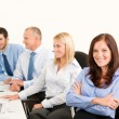 Stock Photo: Business team happy sit in line behind table